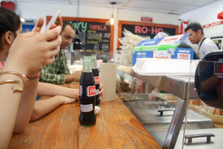 Varios clientes disfrutan tomar Coca-Cola mexicana, hecha con caña de azúcar en vez de la version estadounidense hecha con jarabe de maíz. Foto por Rocío Guenther.