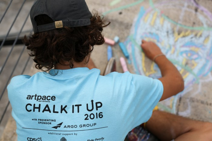 A student from the Henry Ford Academy creates a chalk drawing at Artpace. Photo by Scott Ball.