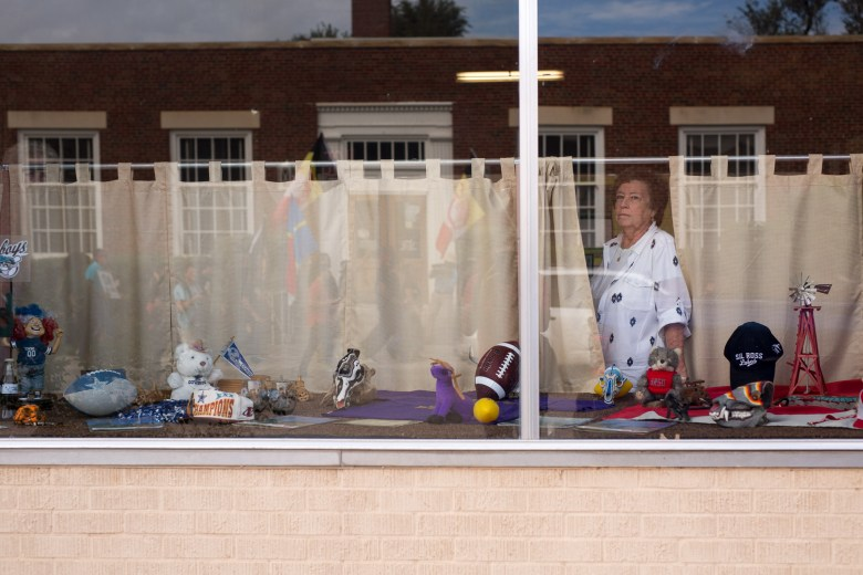 Local store owner Lauris Hawkins peers through her shop window as she hears protestors chant down West Avenue E.