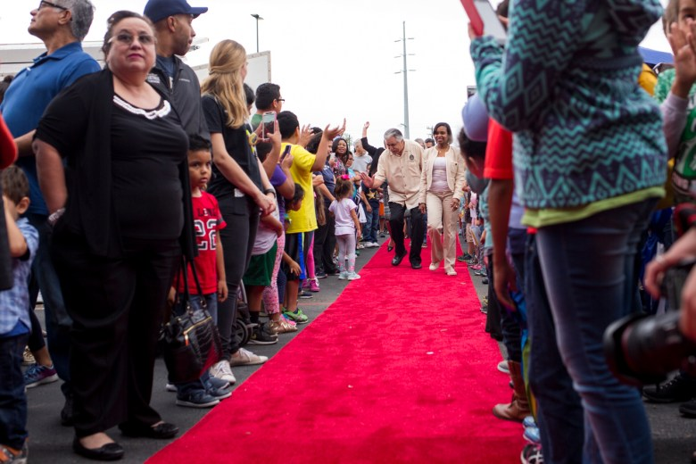 City Councilman (D6) Ray Lopez and Mayor Ivy Taylor walk down a red carpet to the entrance of YMCA.