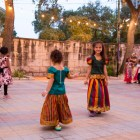 Young children dressed in tradition clothing dance to music.