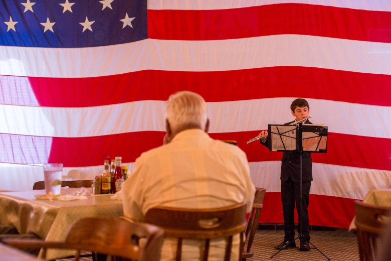 Rommeo Johnson performs the Armed Forces Song on the flute during Veterans Day at Acadiana Cafe.