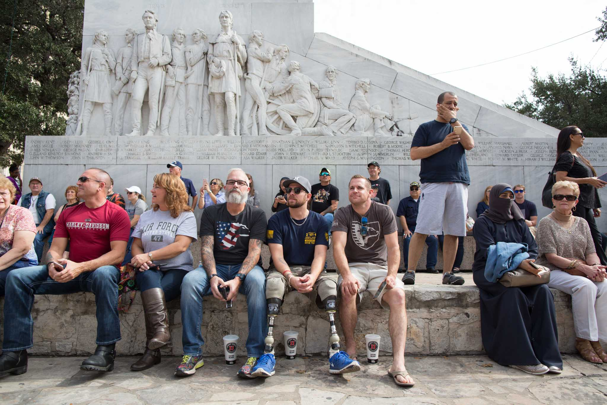"""Attendees of the Veterans Day Parade gather in front of the cenotaph, also known as the """"Spirit of Sacrifice,"""" a monument commemorating the Battle of the Alamo."""