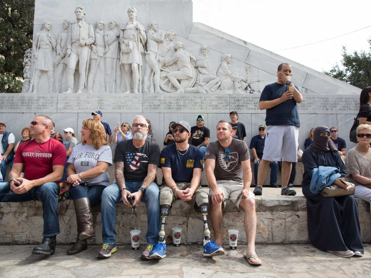 "Attendees of the Veterans Day Parade gather in front of the cenotaph, also known as the ""Spirit of Sacrifice,"" a monument commemorating the Battle of the Alamo."
