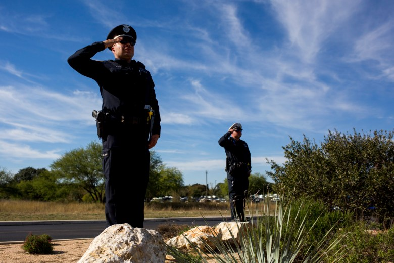 San Antonio Police stand in salut during Detective Marconi's funeral honors.