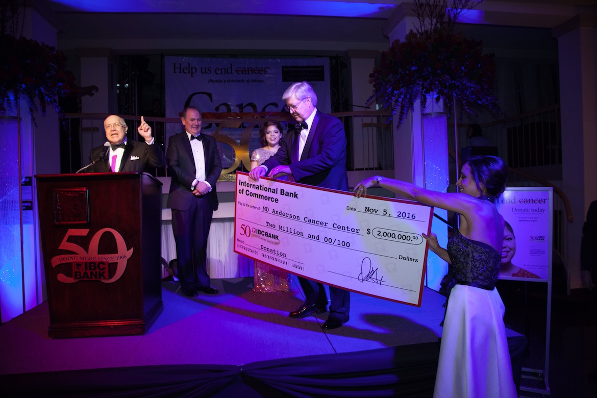 (From left) Gerry Schwebel, executive vice president of IBC Bank, announces the award while IBC Board Chair and CEO Dennis E. Nixon, teen cancer survivor Sabrina Dominguez, and MD Anderson Vice President and Physician in Chief Dr. Thomas Buchholz receive the check.