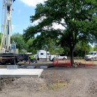 A heritage tree is surrounded by construction equipment (right) as a concrete slab awaits its hut.