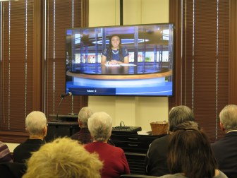 Attendees watch junior mass communications student Chan'Cellore Makanjuola broadcast live from the new production studio.