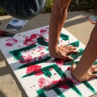 Protestor Aaron Reeh uses red paint to decorate a sign in protest of the Dakota Access Pipeline.