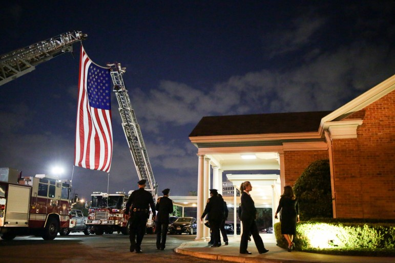 A large American Flag is held by San Antonio Fire trucks outside of Porter Loring Mortuary during the visitation of Detective Benjamin Marconi.