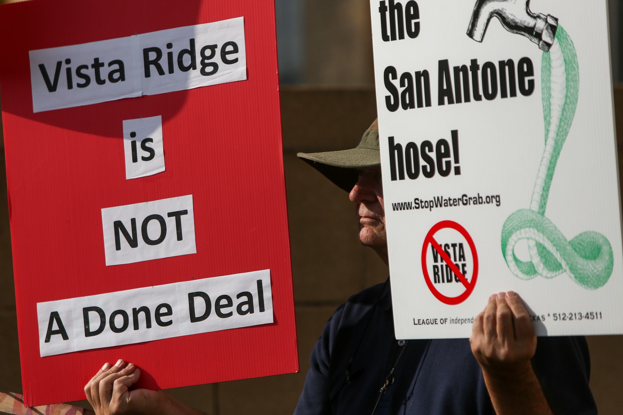 Alan Montemayor holds up two signs in opposition to the Vista Ridge Pipeline which Mayor Taylor strongly supports.