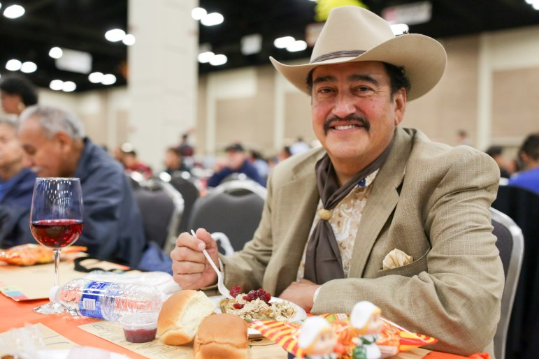 Patron Bobby Torres poses for a photograph as he enjoys his Thanksgiving meal.