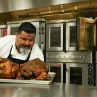 Chef Roy Orozco takes freshly baked turkeys out of the industrial ovens.