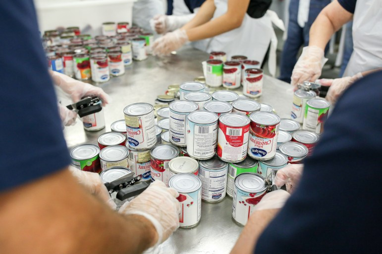 Dozens of canned cranberry sauce is spread across the table to be opened.