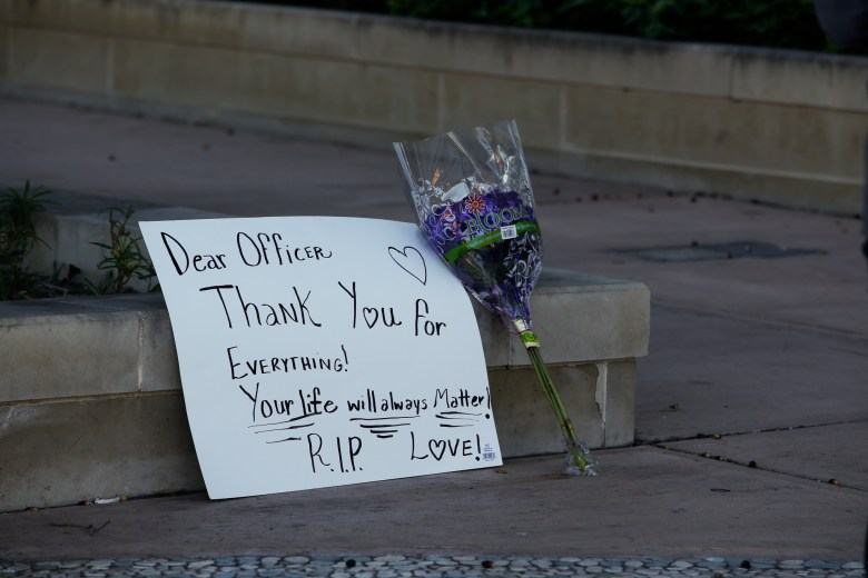 A sign and bouquet of flowers is left in remembrance of fallen San Antonio Police Officer Benjamin Marconi.