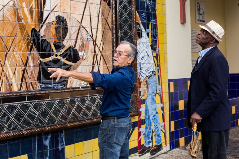Artist Jesse Treviño explains to a passer by how he included himself in the mural.