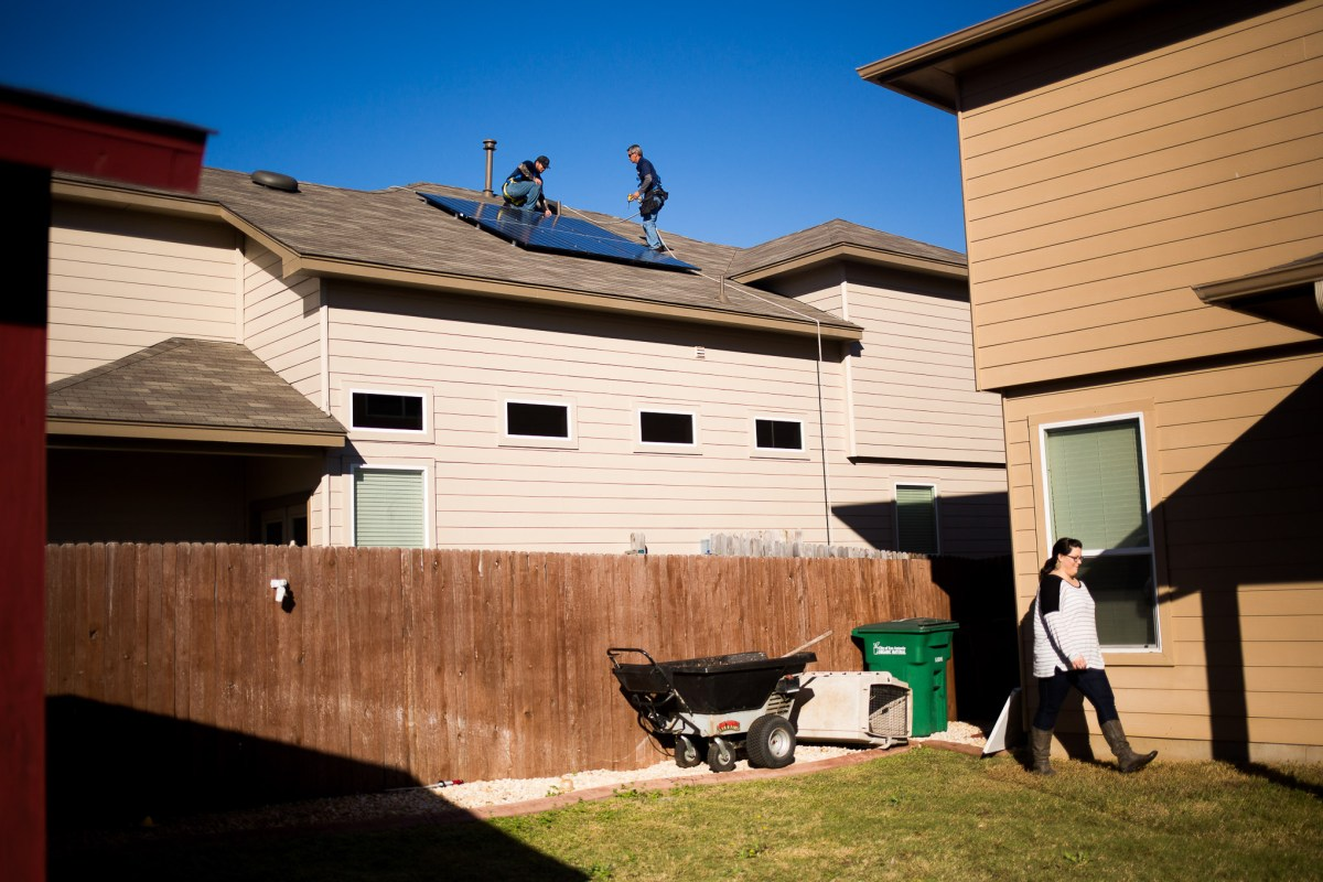 Advanced Solar workers install solar panels on Allison Carrazco's roof.
