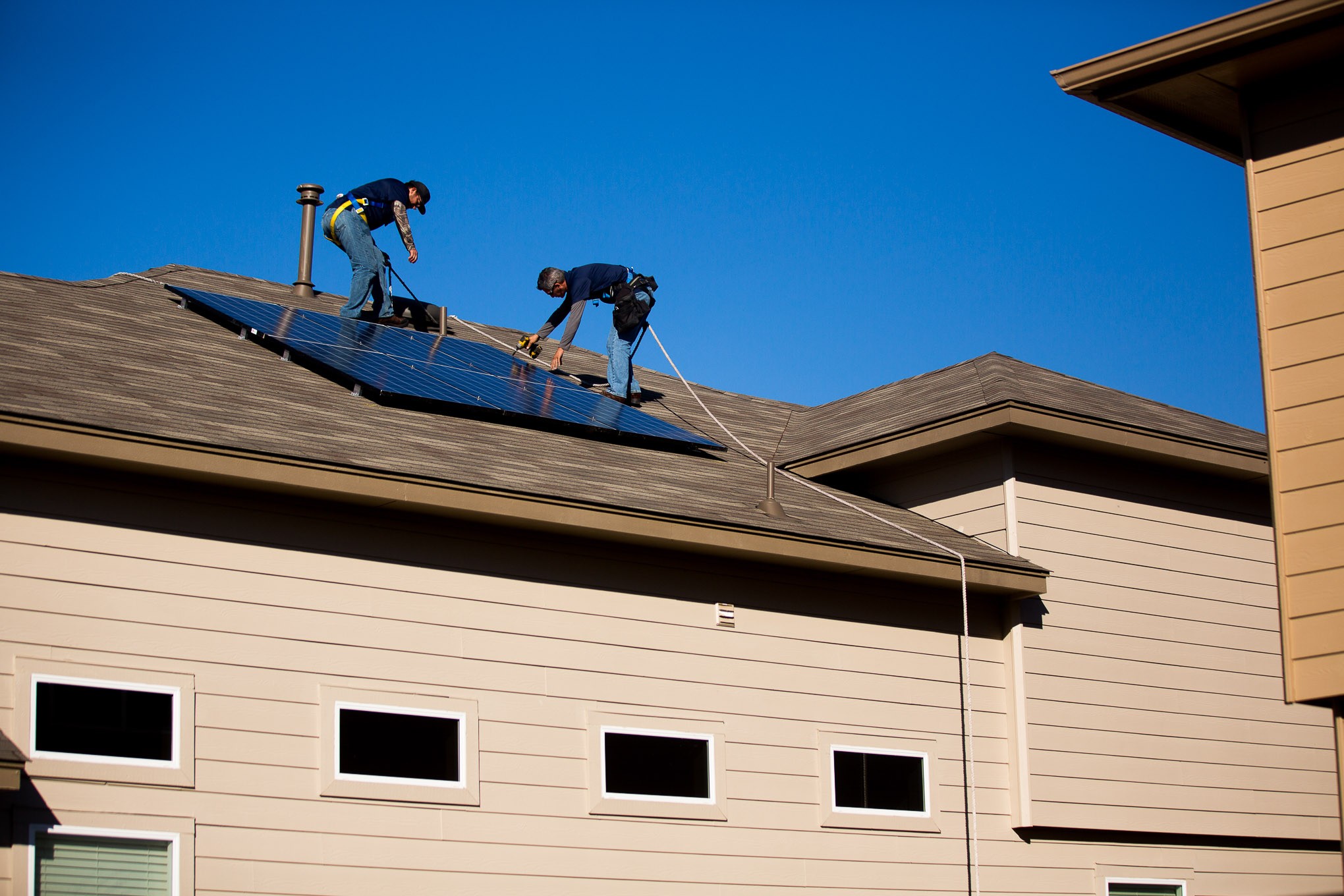 Workers install solar panels on a residential home in 2016. CPS Energy offers rebates to encourage residents to invest in energy-saving home improvements like solar panels.
