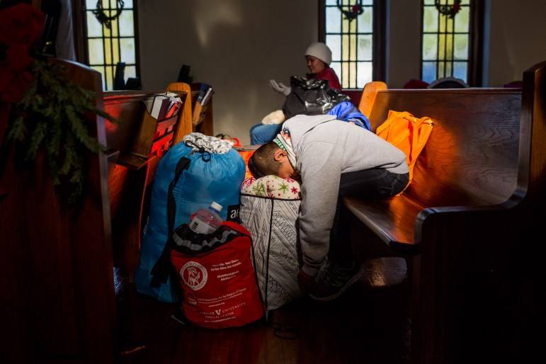 Jose Edilson Ramirez, 11, and rests his head on pile of blankets after a night of sleeping in the cold church with hundreds of other migrants.