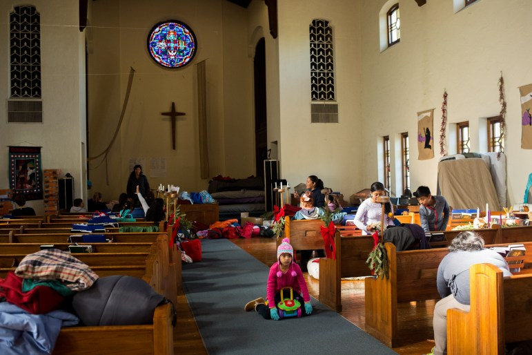 A young migrant plays between the pews of the San Antonio Mennonite Church.