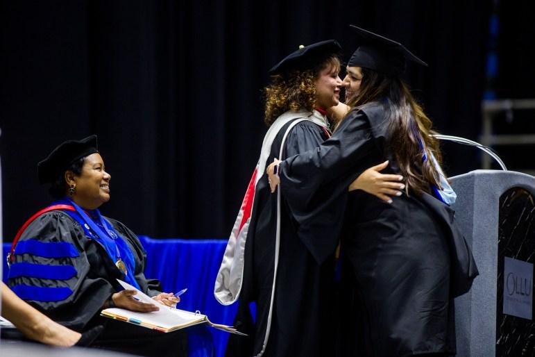Gina García hugs her advisor and Spanish professor Dr. Maribel Lárraga before crossing the stage to graduate.