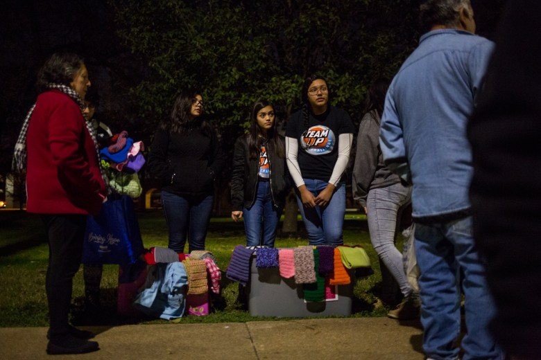 Advanced Learning Academy students look on as people from San Antonio's homeless population line up for food.
