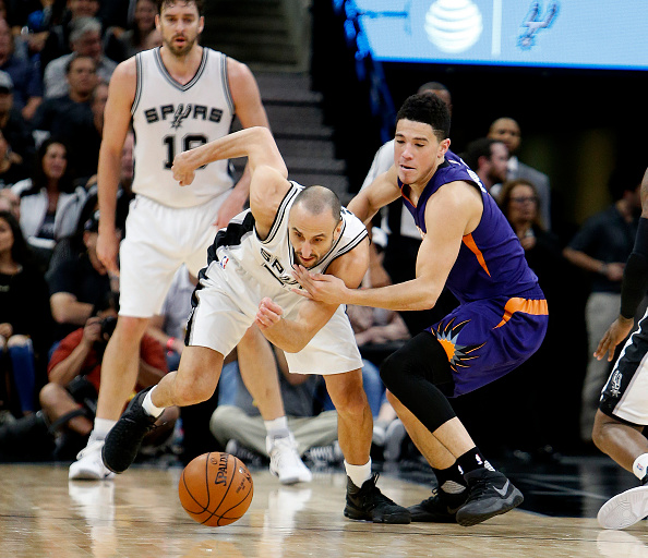 Manu Ginobili #20 of the San Antonio Spurs steals the ball from Devin Booker #1 of the Phoenix Suns at AT&T Center on December 14, 2016 in San Antonio, Texas.