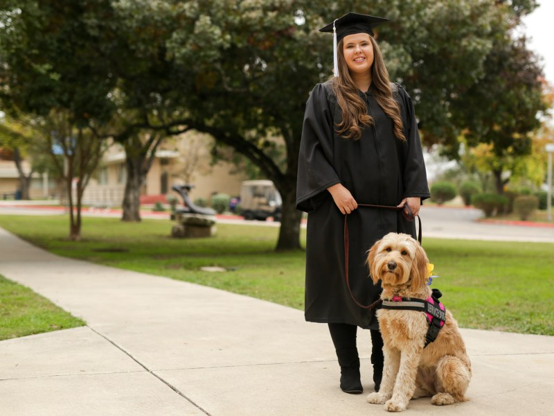 Mikayla Bass poses for a photograph with her service dog Ava.