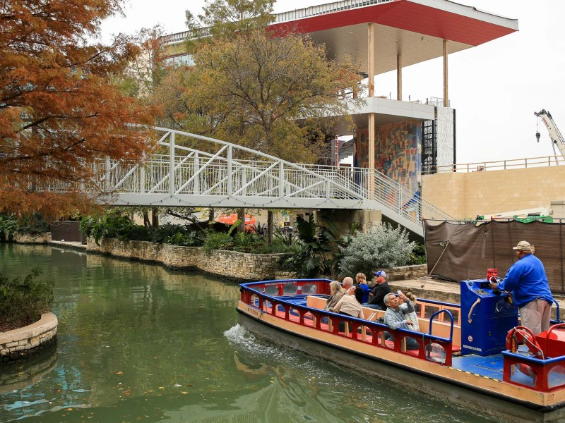 A river barge passes by the construction site working around the mural by artist Carlos Mérida.