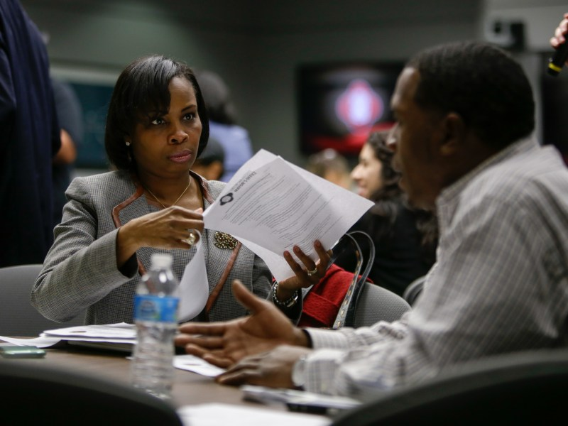 Mayor Ivy Taylor flips through agenda items given to members of the selected council.