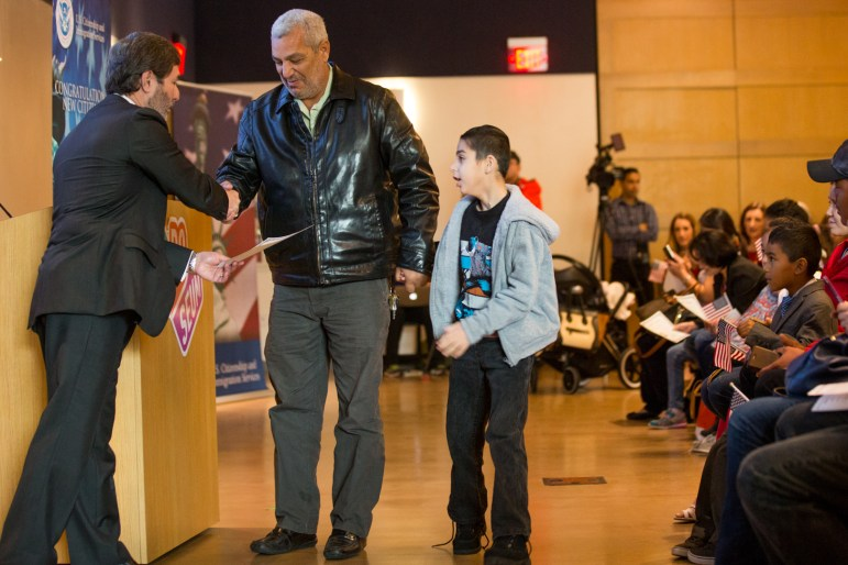Moustafa Altabokhi, 9, from Palestine, accepts his certificate of U.S. citizenship during the naturalization ceremony at the Doseum.