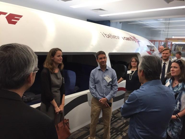 Educate Texas delegates listen to a Singaporean teacher discuss hands-on workforce development alongside a Boeing Dreamliner commercial aircraft learning center.
