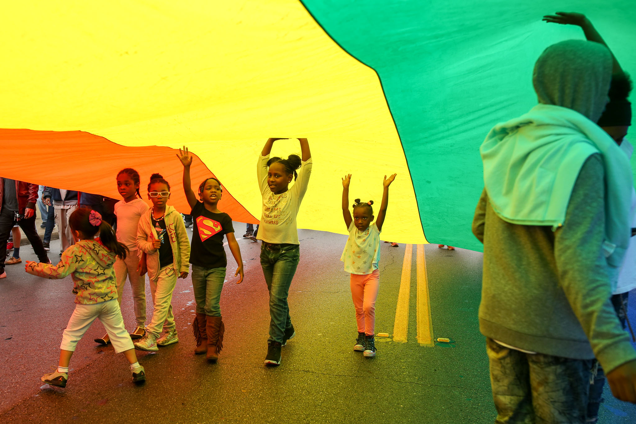 Children hold up a large rainbow colored flag following a large group sign reading 'INCLUSION'.