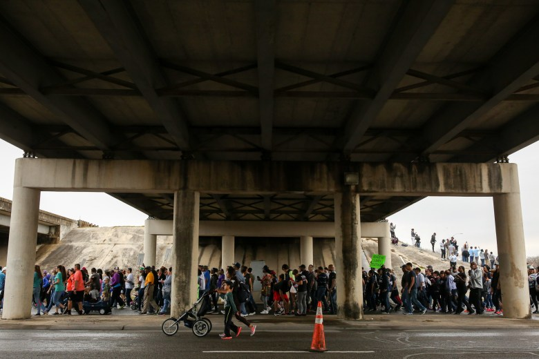 Thousands of participants march through the Interstate underpass heading West on Martin Luther King Drive.