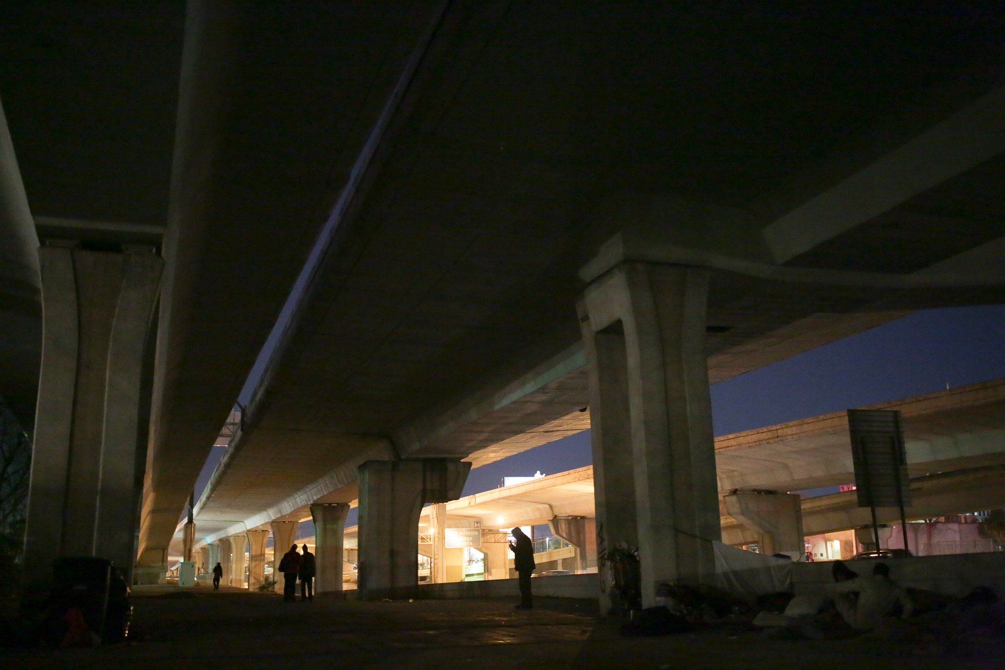 Outreach volunteers and members of the homeless population populate an area under an overpassing highway.