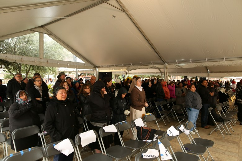 Mourners stand during a song to honor the life of retired Archbishop Patrick Flores.