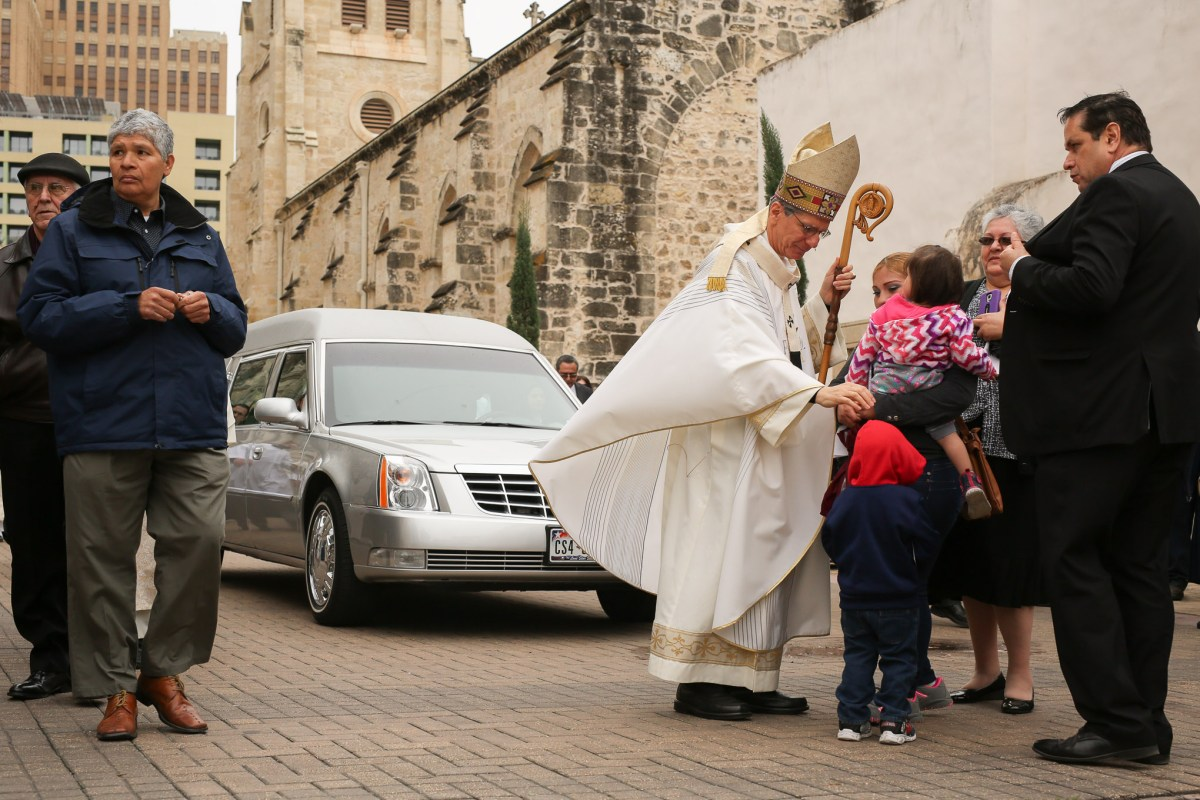 Archbishop Gustavo Garcia-Siller blesses a family near Main Avenue outside San Fernando Cathedral.