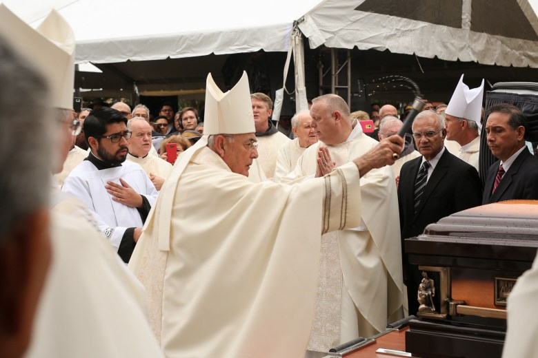 Members of the clergy pay respects to the late Archbishop Flores moments before his casket is delivered to the hearse.
