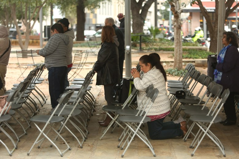 Zee Paiz kneels on the limestone ground as she prays at San Fernando Cathedral.