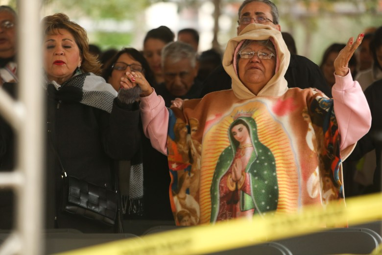 Maria Olivia Valdez prays with others in the outside seating area at San Fernando Cathedral.