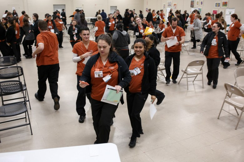 Students in the role-playing exercise hurry to the job placement booth and line up and pay vital bills.