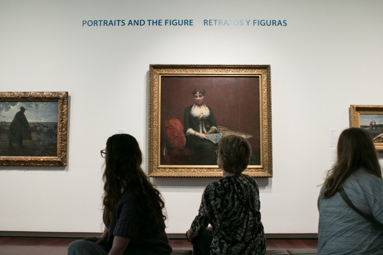 """People gather in front of the piece """"Madame Leon Maitre"""" by Henri Fantin-Latour."""