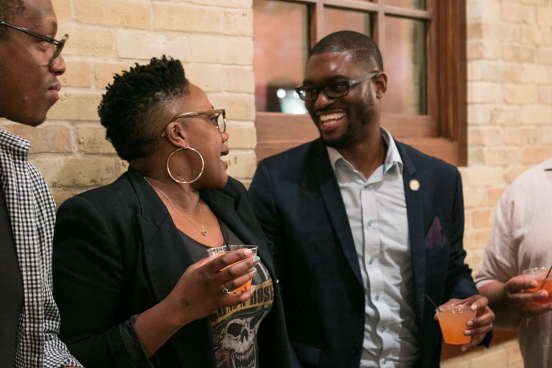 From left, Uche Ogba and Christian Reed-Ogba share a drink during intermission at PechaKucha.