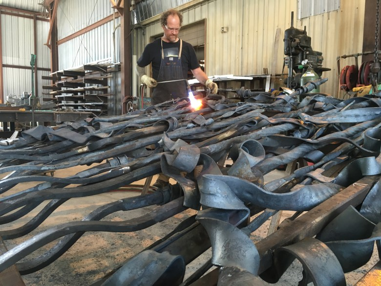 George Schroeder works on the Bodine Gates at his studio near the airport.