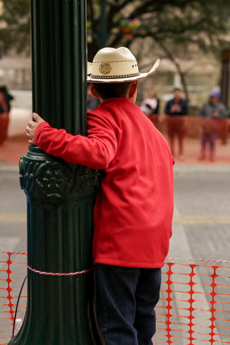 A young boy watches in anticipation as the parade begins to pass by him.