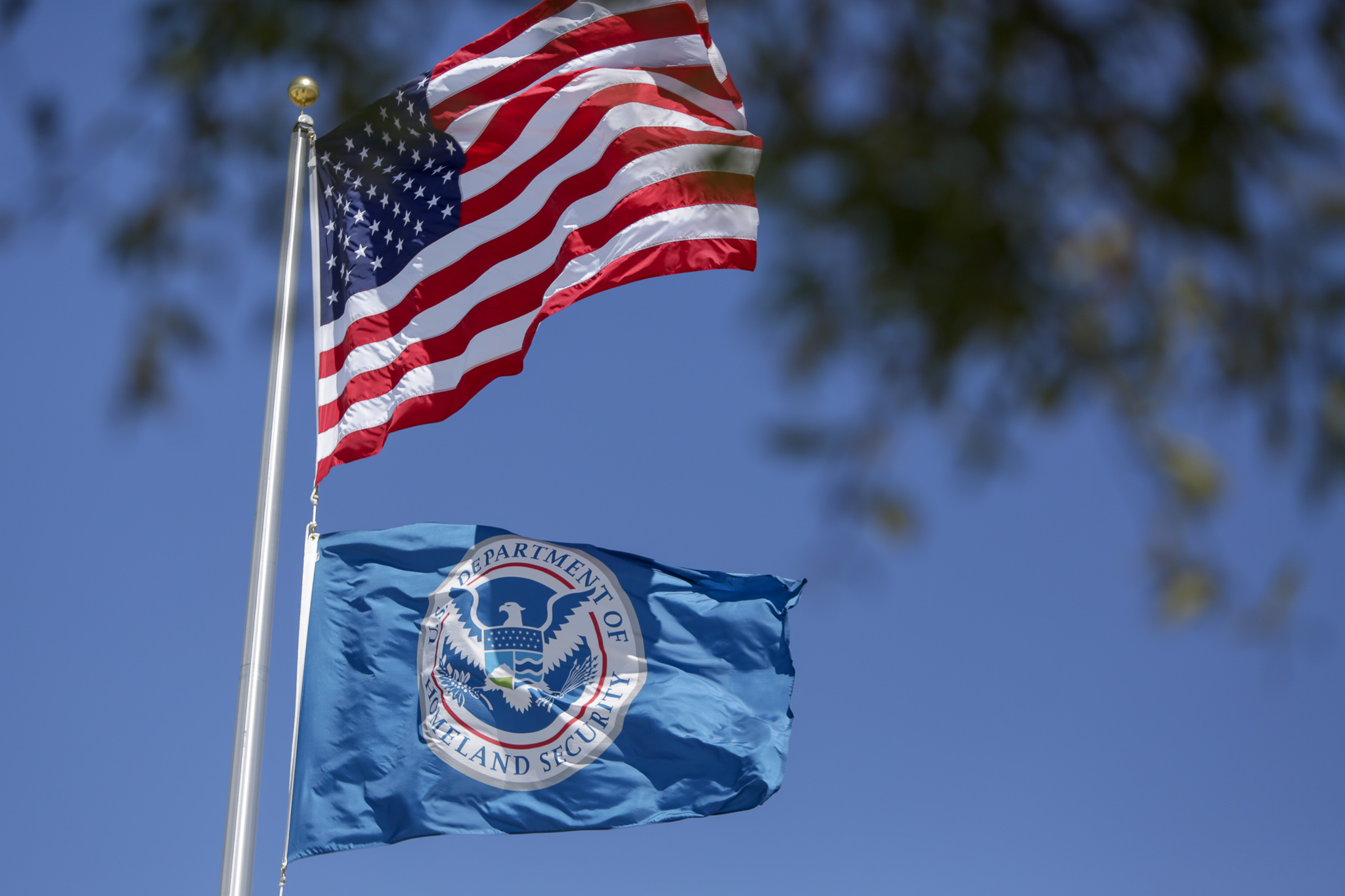 The United States flag and the Department of Homeland Security flag wave outside an ICE (Immigration and Customs Enforcement) office.