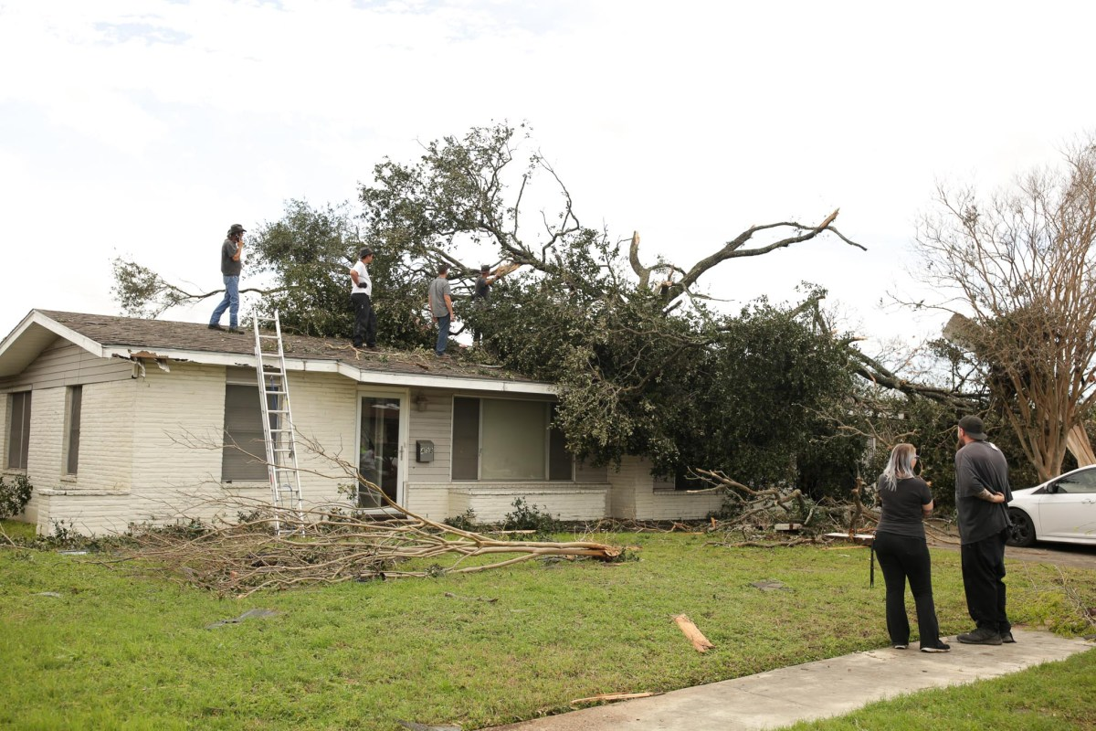 Volunteers and neighbors joint together to remove a large tree laying on the roof of a house on Linda Drive.