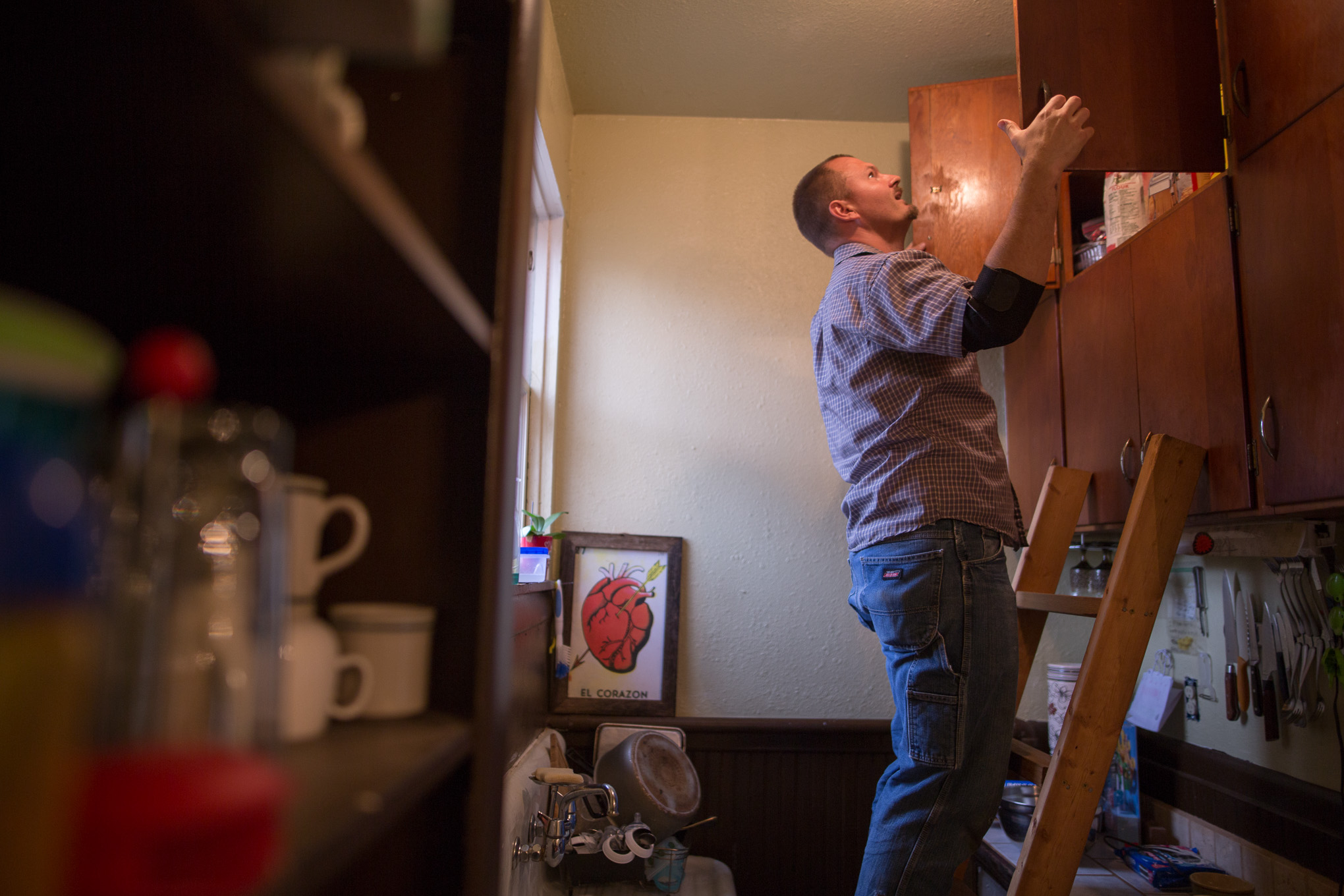 Michael uses his handmade ladder to reach the highly mounted cabinetry.