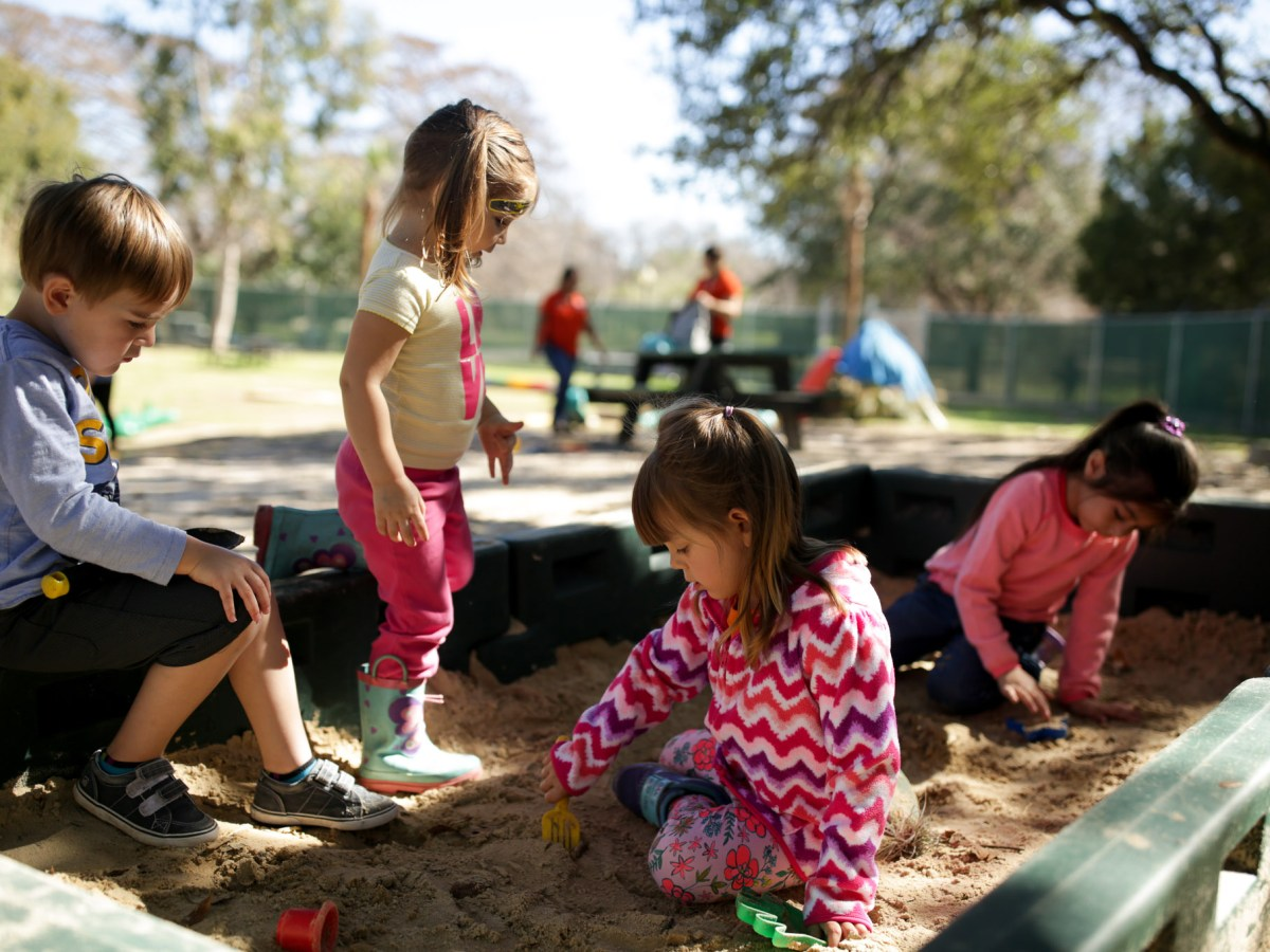 Zoo School classmates play outside in a large sandbox.