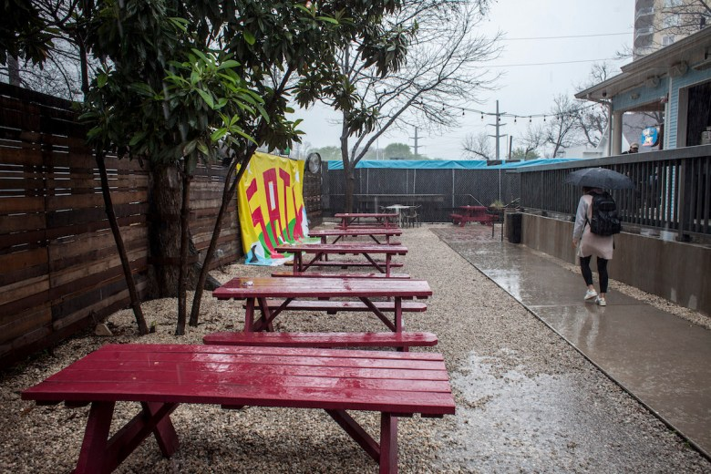 A festival goer walks in the rain during the SXSW ChooseSA event, on Saturday, March 11, 2017 at the Half Step Bar, in Austin.